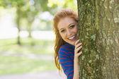 Rossa sorridente nascondendosi dietro un albero — Foto Stock