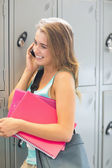 Smiling student talking on the phone beside lockers — Stock Photo