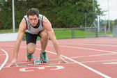 Young man ready to race on running track — Stock Photo