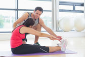 Trainer assisting woman with pilate exercises in fitness studio — Stock Photo