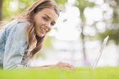 Happy student lying on the grass using her laptop looking at camera — ストック写真