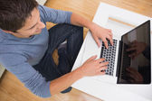 Overhead view of a man using laptop at home — Stock Photo