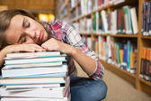 Dozing student sitting on library floor leaning on pile of books — Stock Photo