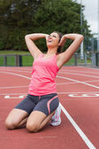Toned woman doing stretching exercise on the running track — Stock Photo