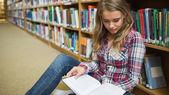 Jovens e belas estudantes sentados no chão de biblioteca, lendo o livro — Fotografia Stock