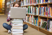 Young student sitting on library floor using laptop on pile of books — Stock Photo