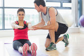 Male trainer assisting woman with pilate exercises in fitness studio — Stock Photo
