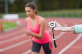 Hand timing a woman's run on the running track — Stock Photo