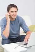 Man using cellphone and laptop in living room — Stock Photo