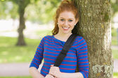 Smiling pretty redhead leaning against a tree — Stock Photo
