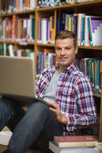 Serious young student sitting on library floor using laptop — Stock Photo