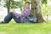 Smiling student using his tablet to study outside — Stock Photo