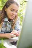 Young student lying on the grass using her laptop — Fotografia Stock