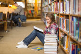 Pretty student reading book on library floor — Stock Photo