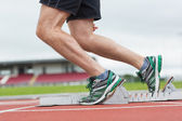 Low section of a man ready to race on running track — Stock Photo