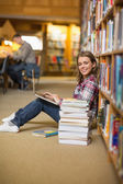 Happy student using laptop on library floor looking at laptop — Stock Photo