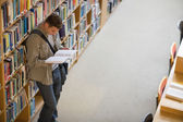 Student reading a book from shelf standing in library — Stock Photo