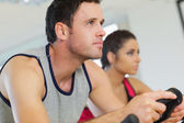 Young man and woman working out at spinning class — Stock Photo