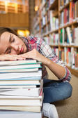 Dozing young student sitting on library floor leaning on pile of books — Stock Photo