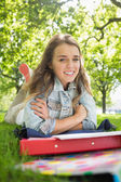 Young pretty student lying on the grass smiling at camera — Stock Photo