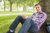 Cheerful student sending a text outside leaning on tree — Stock Photo