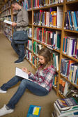 Concentrating student reading book on library floor — Stock Photo