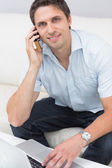 Smiling man using laptop and cellphone in the living room — Stock Photo