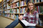 若い学生の本を読んでライブラリの床に座って可愛い — ストック写真