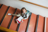 Smiling young student sitting on stairs looking up at camera — Stock Photo