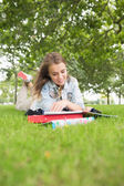 Smiling young student studying on the grass — Stockfoto