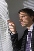 Ernstige zakenman gluren via blinds in office — Stockfoto