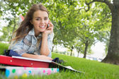 Young pretty student lying on the grass on the phone — Stock Photo