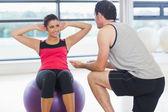 тренер помогает женщине делать брюшной хрустит на фитнес мяче — Стоковое фото