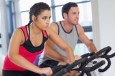Young man and woman working out at spinning class — Foto Stock