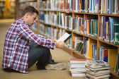 Handsome young student sitting on library floor reading book — Stock Photo