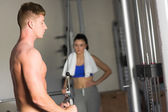Woman looking at determined man use the lat machine in gym — Stock Photo