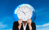 Composite image of businesswoman in suit holding a clock — Stock Photo