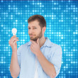 Stock Photo: Handsome model holding bulb