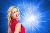Composite image of smiling blonde standing hands on hips — Stock Photo
