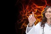 Smiling brunette doctor pointing — Stockfoto