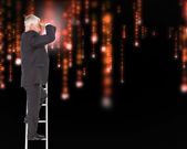 Mature businessman standing on ladder — Stockfoto