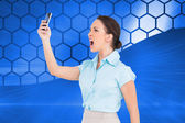 Composite image of angry classy businesswoman yelling at her smartphone — Stock Photo