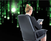 Composite image of businesswoman sitting on swivel chair with tablet — 图库照片