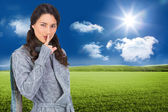 Composite image of young model with winter clothes keeping secret — Stock Photo