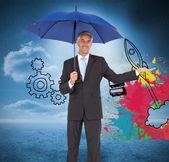 Peaceful businessman holding blue umbrella — Stock Photo