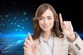 Composite image of classy businesswoman touching invisible screen — Stock Photo