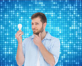 Handsome model holding a bulb — Stock Photo