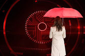Composite image of businesswoman standing back to camera holding red umbrella — Foto de Stock
