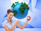 Businesswoman indicating alarm clock — Stock Photo