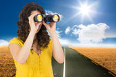 Composite image of casual young woman using binoculars — Stock Photo